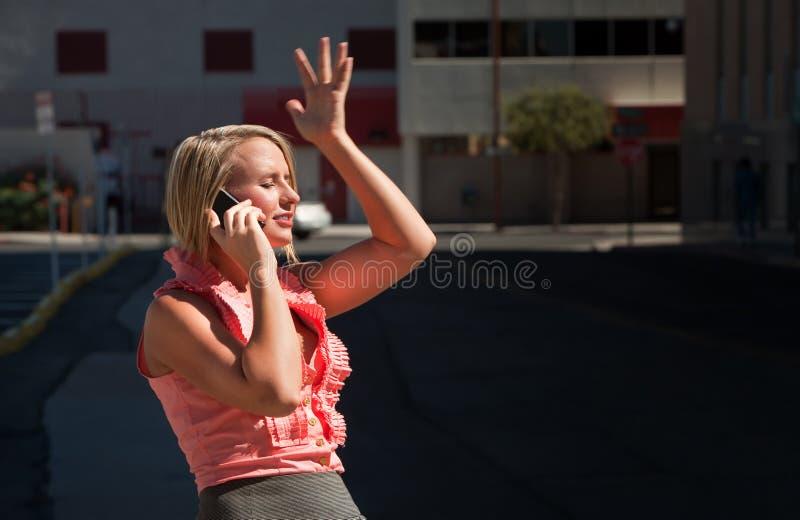 La ragazza graziosa ha momento ah-ha che comunica sul telefono delle cellule immagine stock