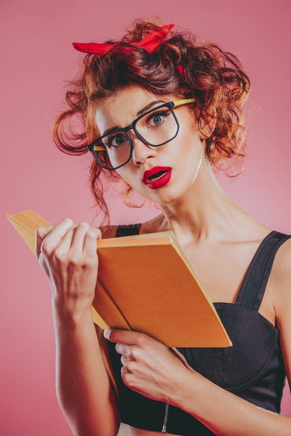 La ragazza graziosa legge il libro fotografia stock libera da diritti