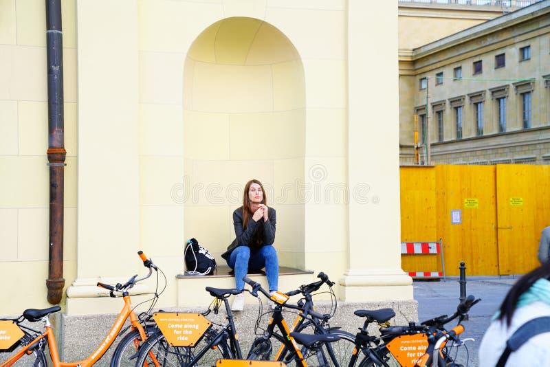 La ragazza graziosa nel posto adatto di seduta della ragazza della parete che torce i capelli tramite il noleggio va in biciclett fotografie stock libere da diritti