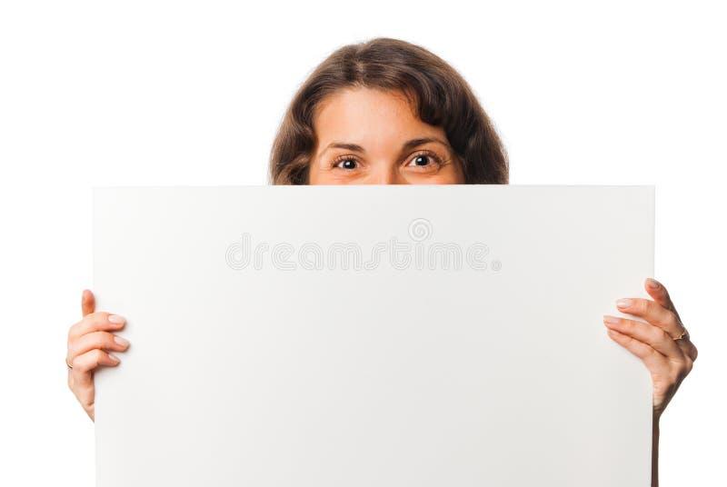 La ragazza graziosa pigola fuori da dietro la scheda in bianco fotografia stock