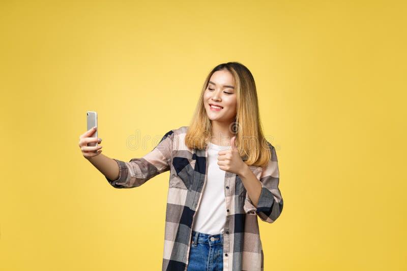 La ragazza graziosa prende un autoritratto con il suo Smart Phone Selfie asiatico della ragazza, isolato su fondo giallo fotografie stock libere da diritti