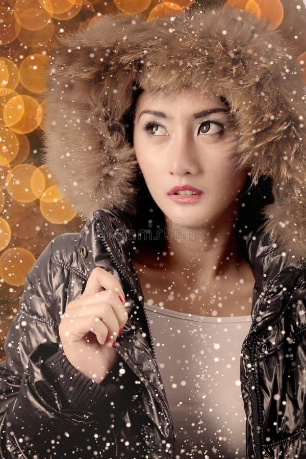 La ragazza graziosa sembra pensierosa nell'ambito delle precipitazioni nevose immagini stock libere da diritti