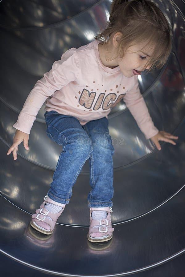La ragazza graziosa si diverte su uno scorrevole nel campo da giuoco fotografie stock