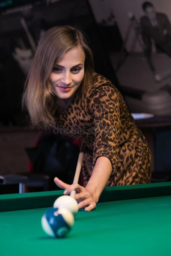 La ragazza graziosa sta giocando il biliardo immagini stock libere da diritti