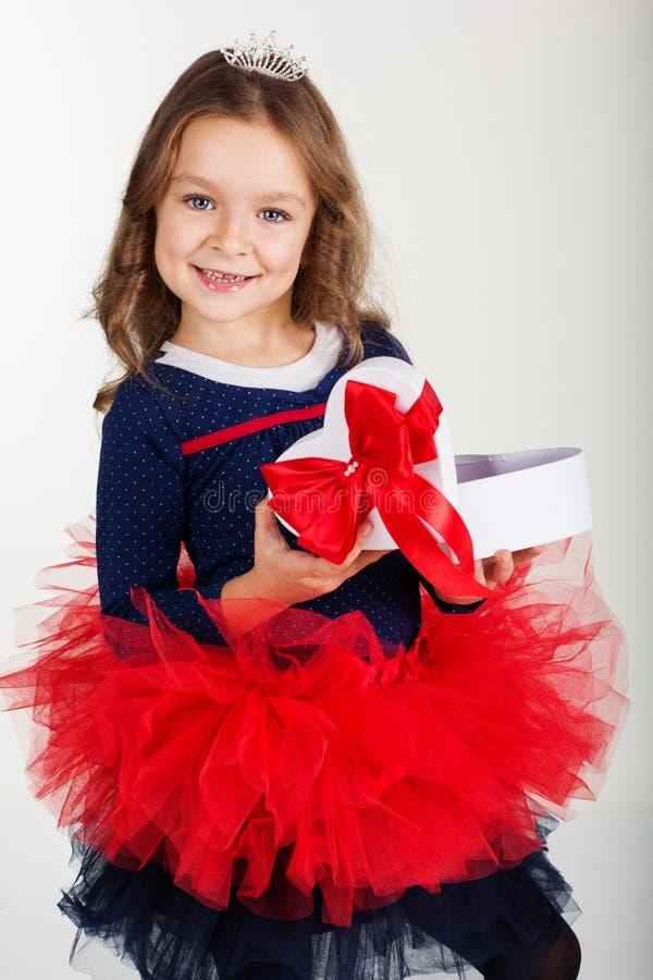 La ragazza graziosa sta tenendo il contenitore di regalo con il nastro rosso immagine stock libera da diritti