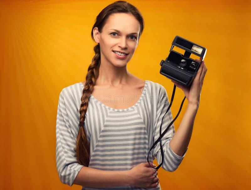 La ragazza graziosa tiene una retro macchina fotografica fotografia stock