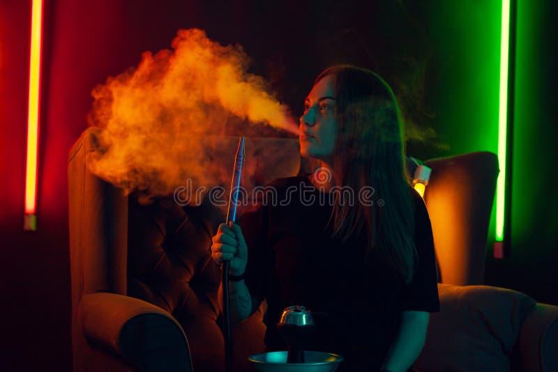 La ragazza graziosa in una maglietta nera sta fumando un narghilé che esala un fumo ad un night-club di lusso fotografia stock libera da diritti