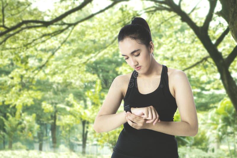 La ragazza graziosa usa lo smartwatch al parco immagine stock