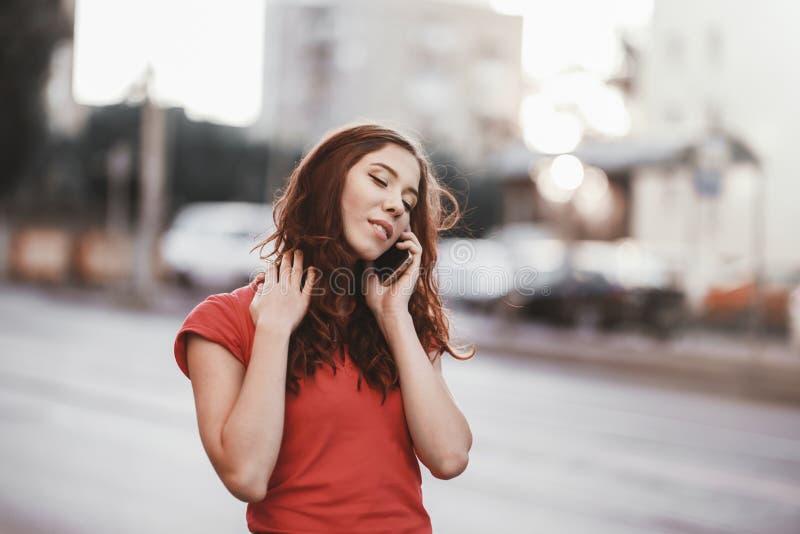 La ragazza graziosa in vestito casuale sta parlando su un telefono cellulare mentre camminava alla via della città su un tempo de fotografia stock libera da diritti