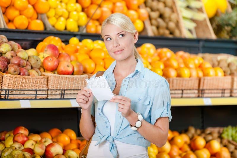 La ragazza guarda attraverso la lista di acquisto vicino al mucchio dei frutti fotografia stock