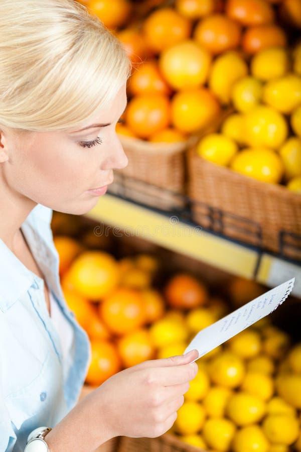 La ragazza guarda attraverso la lista di acquisto vicino alla pila di frutti immagine stock