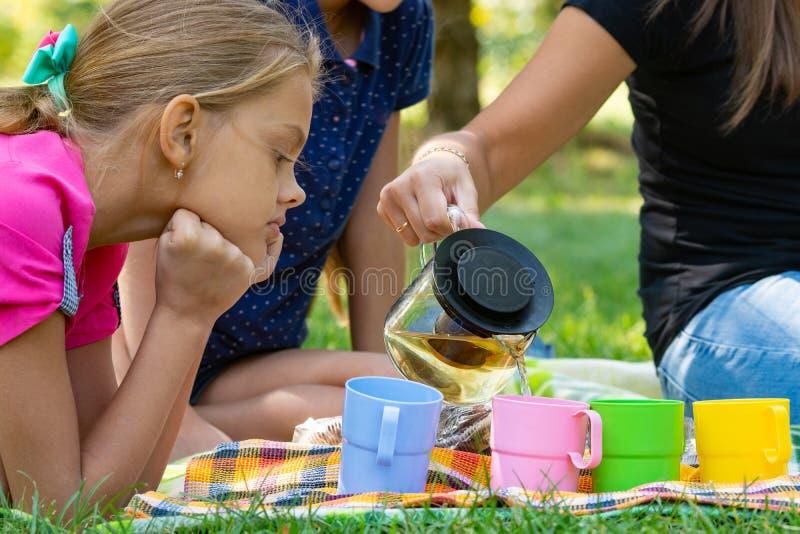 La ragazza guarda con interesse mentre la ragazza versa il tè in bicchieri fotografie stock libere da diritti