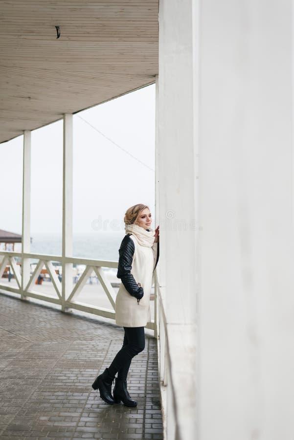 La ragazza guarda fuori da dietro la colonna nella distanza fotografia stock