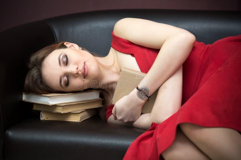 La ragazza ha abbracciato il libro ed i sonni sullo strato fotografia stock