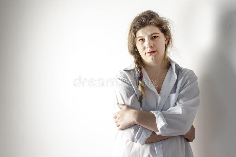 La ragazza ha circa 30 anni dietro è quasi tutta la parete bianca sulla ragazza la camicia è bianca abbia tonalità la ragazza non immagine stock libera da diritti