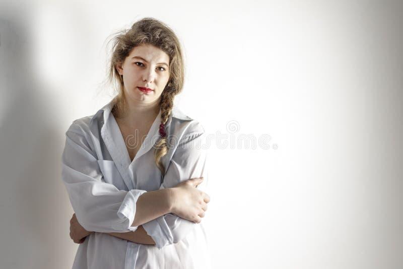 La ragazza ha circa 30 anni dietro è quasi tutta la parete bianca sulla ragazza la camicia è bianca abbia tonalità la ragazza non immagini stock libere da diritti