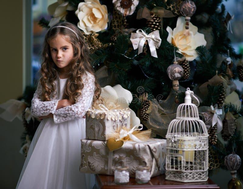La ragazza ha fatto smorfie vicino ai regali di Natale immagine stock