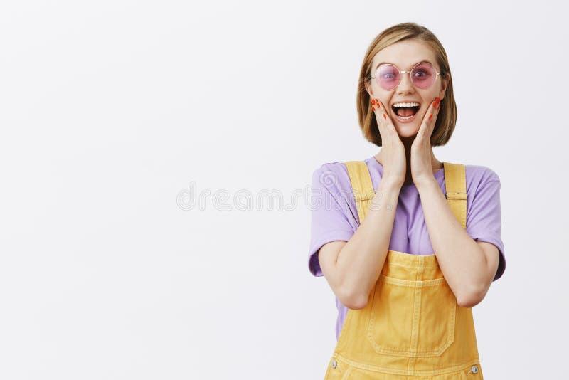 La ragazza ha vinto i biglietti al festival di musica, stante in camici ed occhiali da sole gialli svegli, sorridere allegro e gu fotografia stock