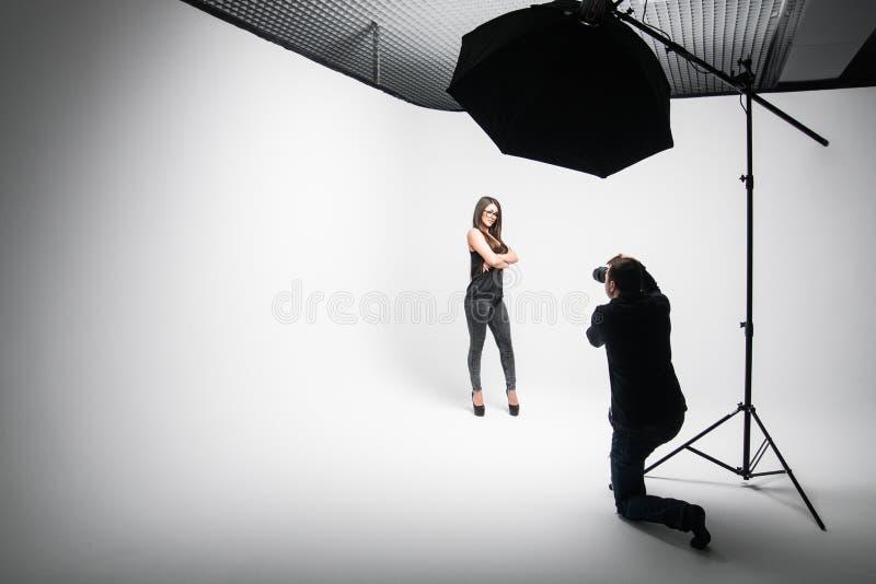 La ragazza il fotografo prende le immagini del modello nel nero su un fondo bianco immagine stock libera da diritti