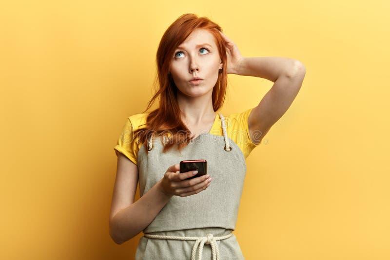 La ragazza imbarazzata non conosce che cosa scrivere al suo amico, fotografia stock libera da diritti