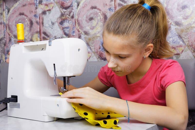 La ragazza impara cucire immagini stock libere da diritti
