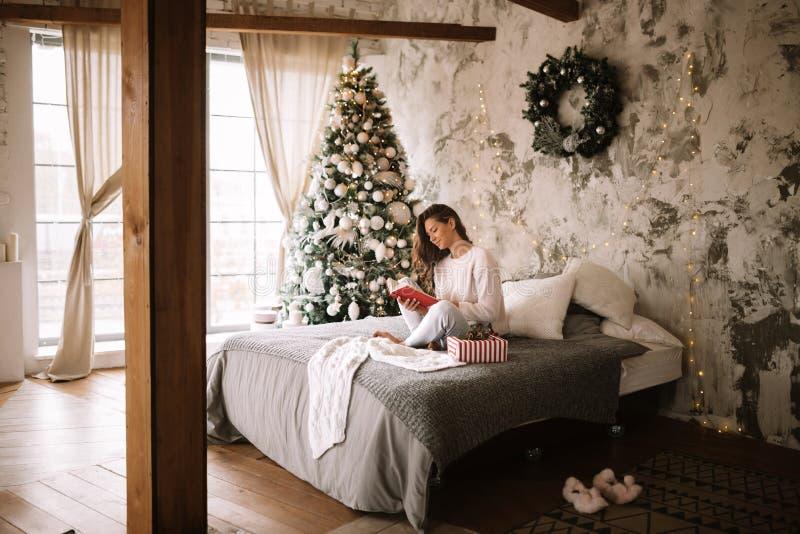 La ragazza incantante vestita in maglione e pantaloni bianchi legge un libro che si siede sul letto con la coperta grigia, i cusc immagini stock libere da diritti