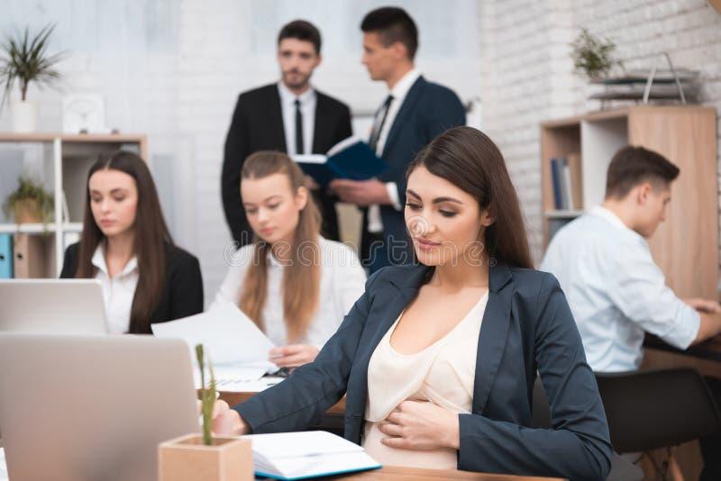 La ragazza incinta attraente sta lavorando nell'ufficio con i colleghi Donna di affari incinta nell'area di lavoro Ragazza incint fotografia stock libera da diritti