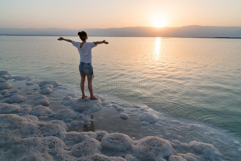 La ragazza incontra l'alba sulla riva il mar Morto fotografia stock