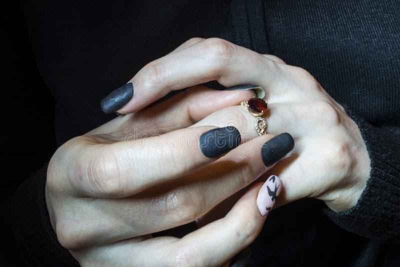La ragazza indossa un anello con un granato di pietra rosso sul suo dito fotografie stock libere da diritti