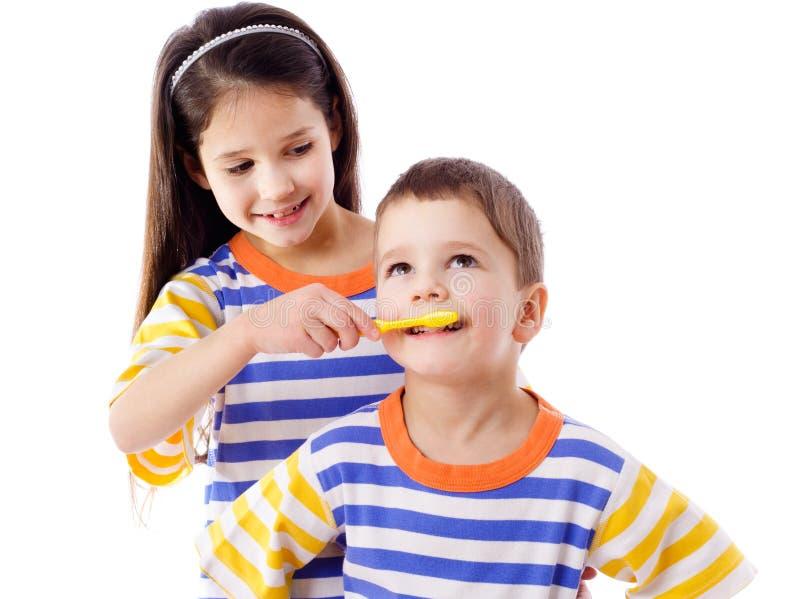 La ragazza insegna ad un ragazzo a pulire i vostri denti fotografia stock