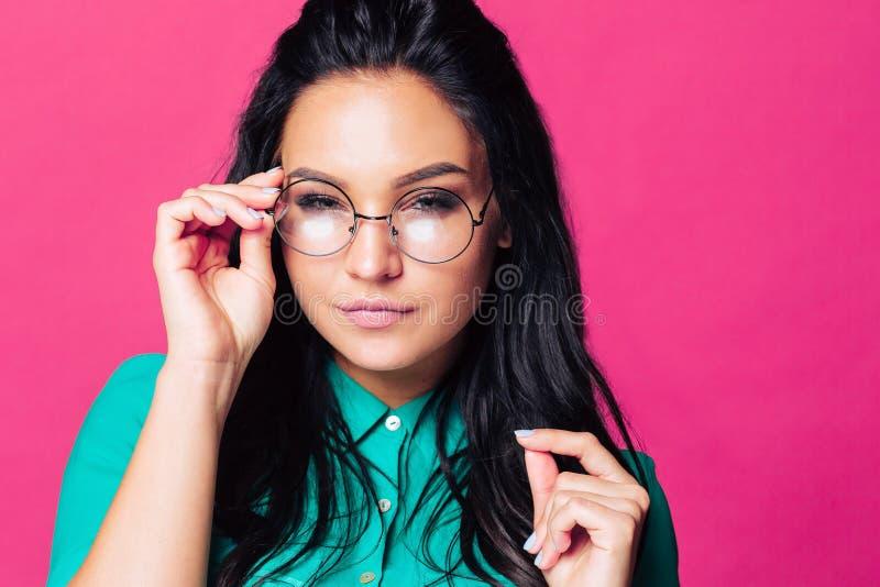 La ragazza insidiosa con i vetri su un fondo di rosso indica il suo dito alla macchina fotografica immagini stock