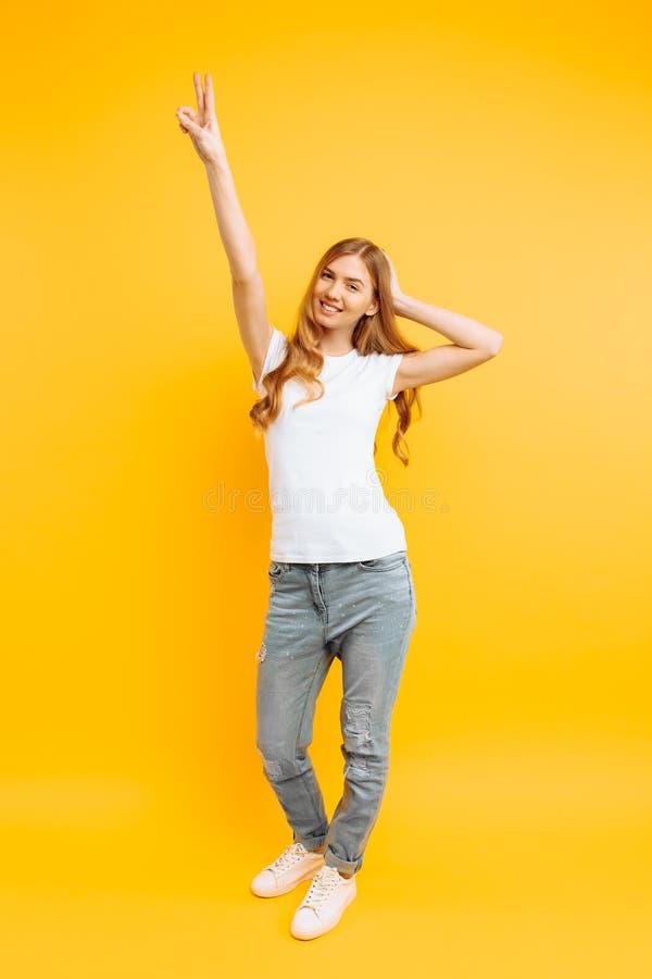 La ragazza integrale e positiva, mostra un gesto pacifico, due dita, su un fondo giallo immagini stock libere da diritti