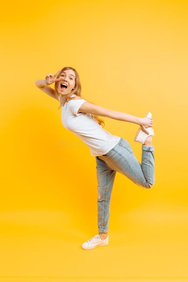 La ragazza integrale e positiva, mostra un gesto pacifico, due dita, su un fondo giallo immagine stock libera da diritti