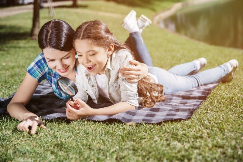 La ragazza interessata ed astuta sta trovandosi sulla coperta con la sua mamma e sta tenendo il ciclo in mani Sta domandandosi La fotografia stock libera da diritti
