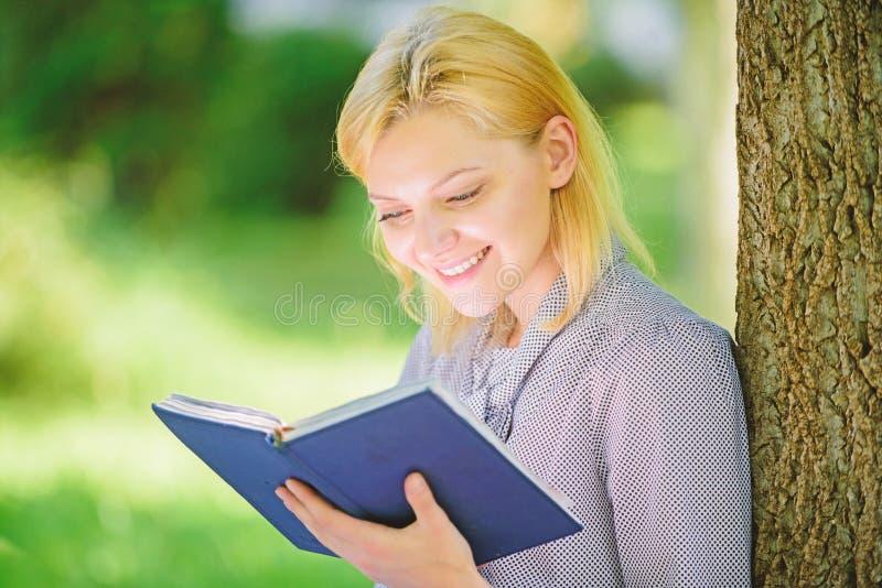La ragazza interessata si siede il fondo della natura del libro colto parco Lettura dei libri d'ispirazione Letteratura femminile fotografia stock