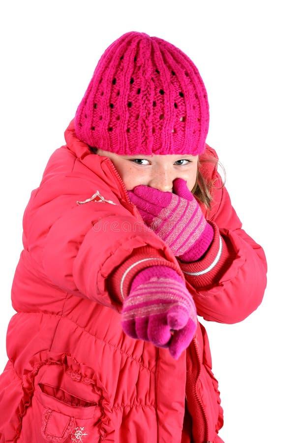 La ragazza in inverno copre la risata indicando una barretta fotografia stock