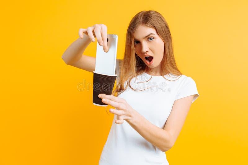 La ragazza irritata con rabbia ha abbassato il telefono in un vetro di caffè, su un fondo giallo fotografia stock libera da diritti