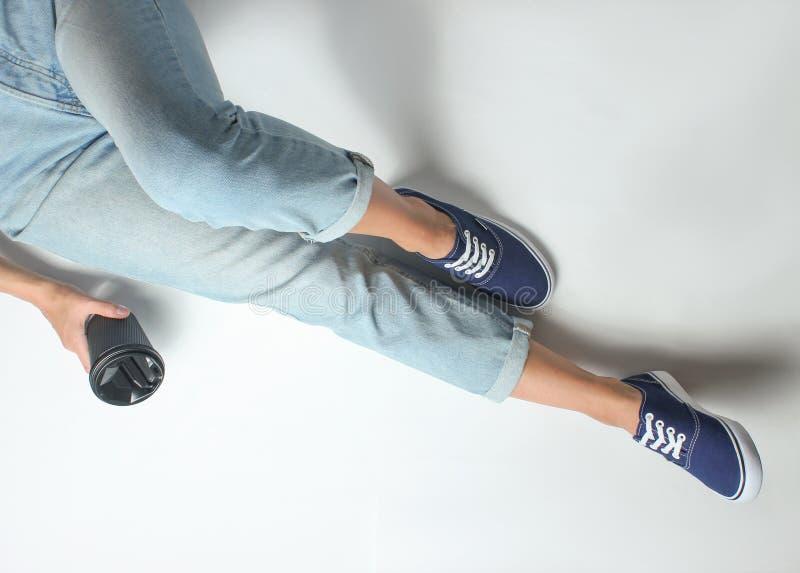 La ragazza in jeans e scarpe da tennis si siede su un fondo bianco immagini stock libere da diritti