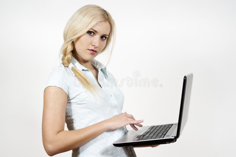 La ragazza lavora ad un computer portatile immagine stock libera da diritti