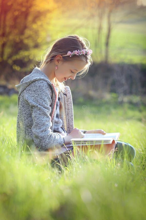La ragazza legge un libro nella natura immagini stock