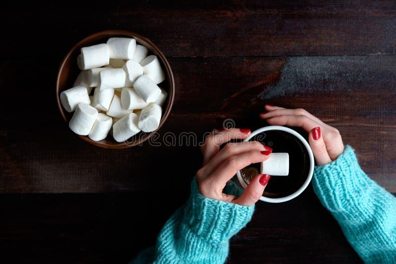 La ragazza in maglione blu che tiene la tazza di caffè passa la ciotola del primo piano di fotografie stock