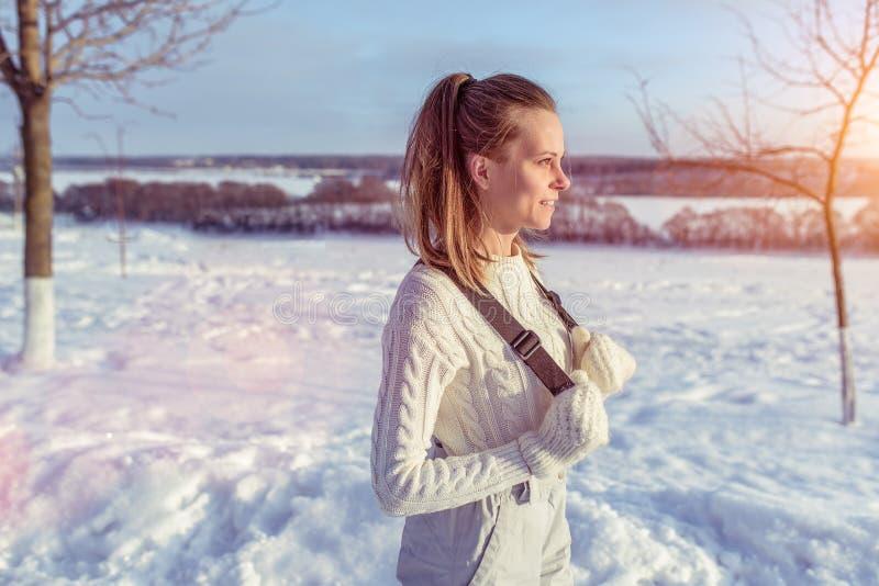 La ragazza in maglione caldo e camici nell'inverno in aria fresca Neve e derive degli alberi del fondo Spazio libero per fotografia stock libera da diritti