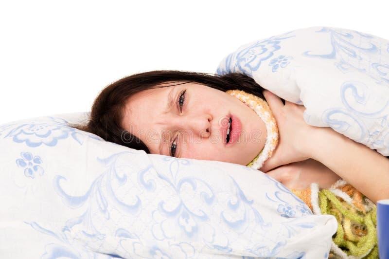 La ragazza malata che si trova sul letto, una gola irritata immagine stock libera da diritti