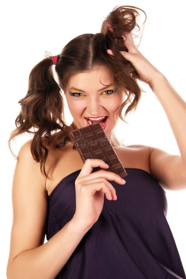 La ragazza mangia il cioccolato immagine stock