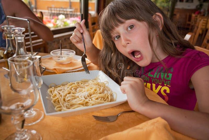 La ragazza mangia la pasta in ristorante italiano fotografia stock