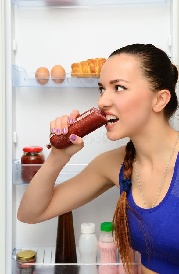 La ragazza mangia la salsiccia vicino al frigorifero immagini stock libere da diritti