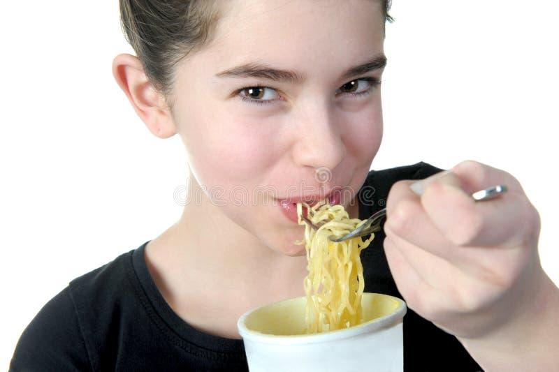 La ragazza mangia le tagliatelle fotografia stock libera da diritti
