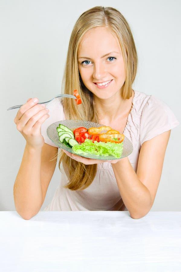 La ragazza mangia le verdure immagine stock