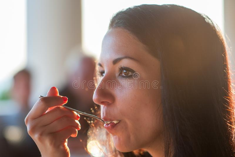La ragazza mangia un primo piano del cucchiaio Una donna sta godendo di un pasto delizioso in pieno della bocca Raggi di Sun alim fotografia stock libera da diritti