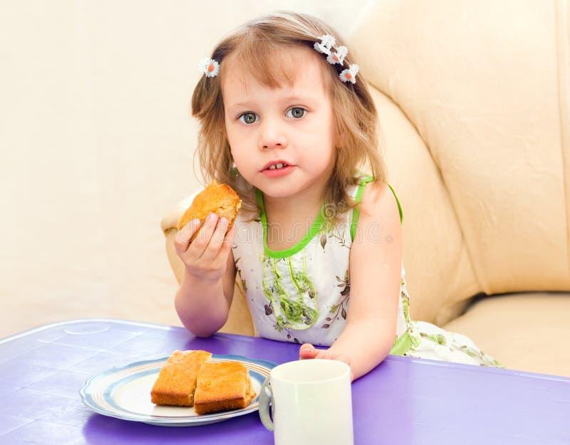 La ragazza mangia una parte del grafico a torta fotografia stock